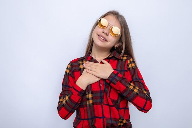 白い壁に隔離された赤いシャツと眼鏡を身に着けている美しい少女の心に手を置いて喜んで