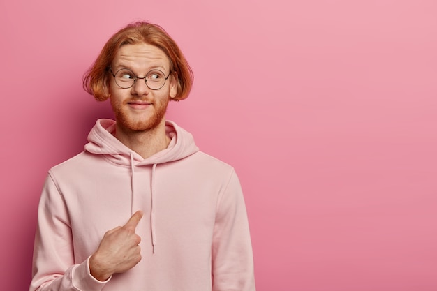 Pleased redhead man with bob hairstyle and ginger hair, points at himself and looks in wonder aside, wears optical glasses and sweatshirt, asks do you mean me, poses against rosy pastel wall