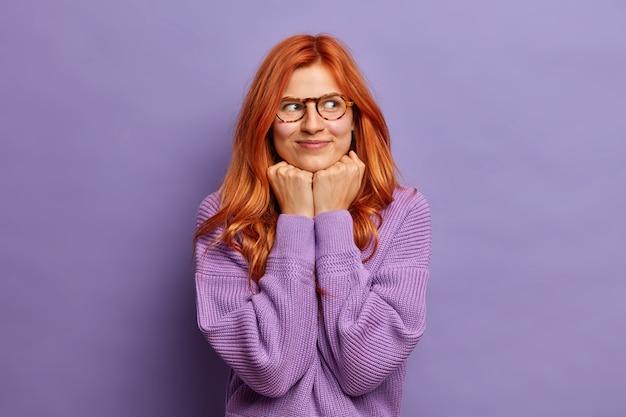 喜んでいる赤毛の女性は、あごの下に手を集中させて脇に置き、夢のような表情で光学メガネと紫のセーターを着ています。