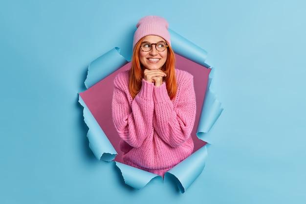 기쁘게 빨간 머리 젊은 여자는 턱 미소 아래에 손을 즐겁게 유지하고 멀리 보이는 것은 매우 좋고 즐거운 것을 생각하며 겨울 스웨터 모자 안경을 착용합니다.