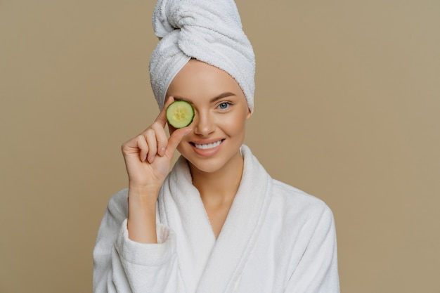 Pleased refreshed woman covers eye with slice of fresh cucumber cares about skin
