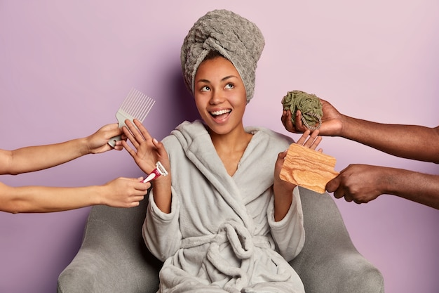 満足しているリラックスした女性は頭にバスローブと包まれたタオルを着ています