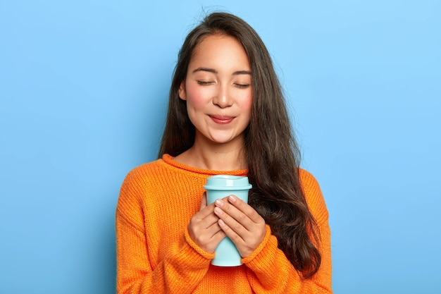 Довольная, спокойная девушка азиатской внешности, держит глаза закрытыми, нежно улыбается, любит пить ароматный эспрессо из чашки на вынос, носит оранжевый джемпер
