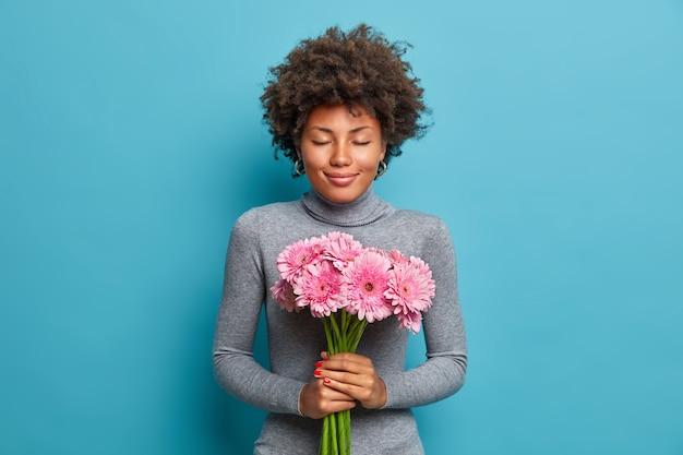 기쁘게 낭만적 인 아프리카 계 미국인 여자가 거베라 꽃의 아름다운 꽃다발을 보유하고 있습니다.