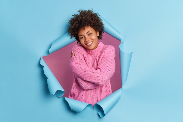 Pleased romantic happy young afro american woman embraces herself needs feel warmth and love recalls lovely memory wears knitted sweater breaks through paper wall