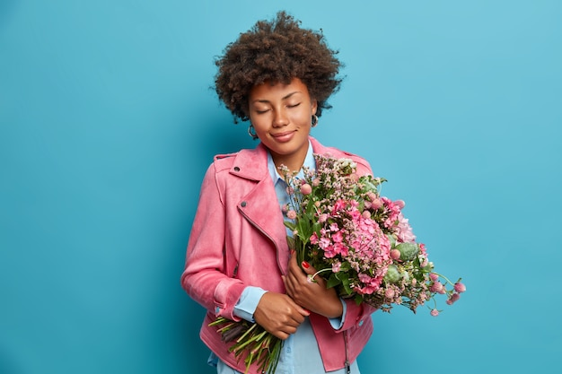 Pleased romantic woman gets beautiful bouquet as present, closes eyes and smiles gently, dressed in pink jacket