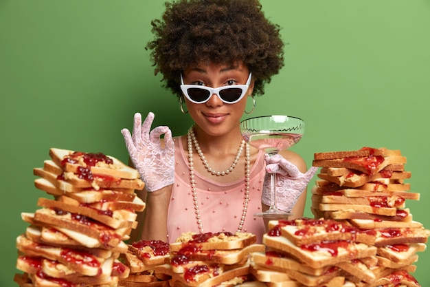 Pleased satisfied lady approves nice alcoholic beverage, makes okay gesture, poses with glass , wears elegant dress and necklace, spends free time on banquet, surrounded by sandwiches