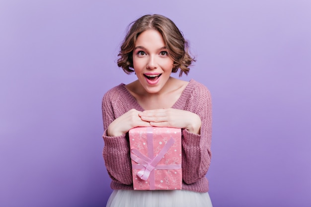 Pleased short-haired woman posing with cute pink present box and smiling. enchanting curly girl enjoying photoshoot with new year gift on purple wall.