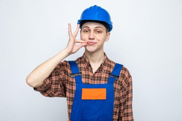 Lieto di mostrare un gesto delizioso giovane costruttore maschio che indossa l'uniforme