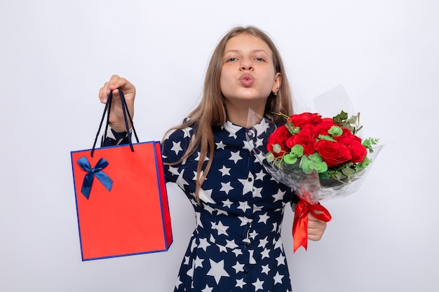 Pleased showing kiss gesture beautiful little girl holding bouquet with gift bag