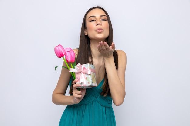 흰색 벽에 고립 된 꽃과 선물을 들고 키스 제스처를 보여주는 기쁘게 생각 하는 아름 다운 젊은 여자