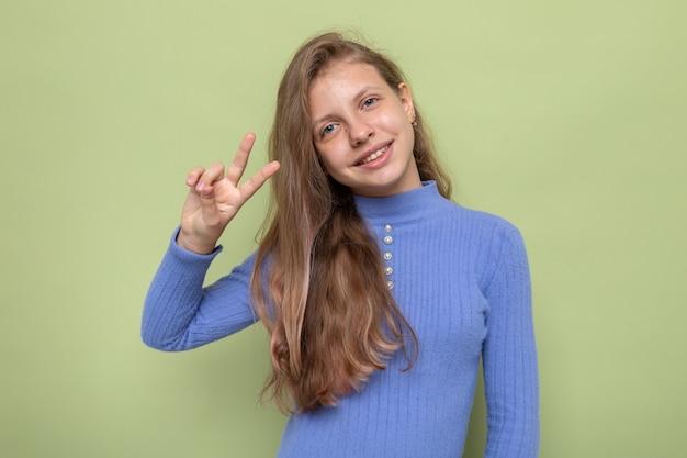 平和のジェスチャーを示すことを喜んでオリーブグリーンの壁に分離された青いセーターを着ている美しい少女