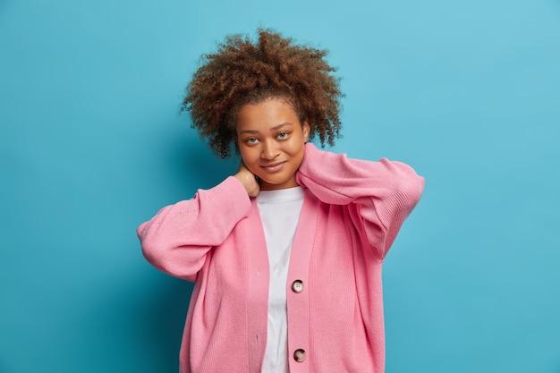 아프로 머리를 가진 기뻐하는 수줍은 여성은 목에 손을 얹고 직접 만족스럽게 보이는 캐주얼 장밋빛 점퍼를 입어 진지한 감정을 표현한다.