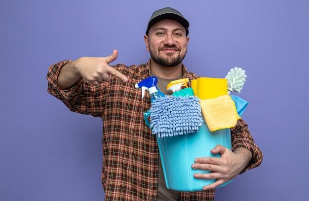 Compiaciuto uomo delle pulizie slavo che tiene e indica le attrezzature per la pulizia