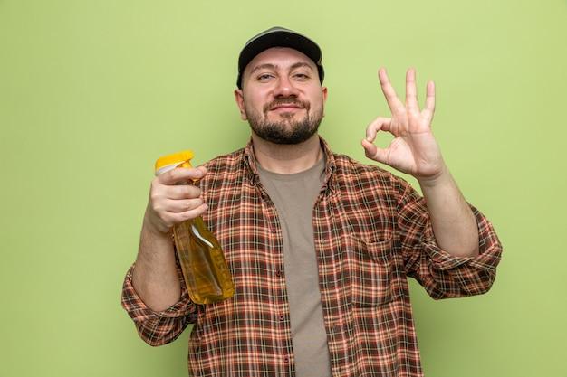 Felice uomo delle pulizie slavo che tiene in mano un detergente spray e fa un gesto ok segno