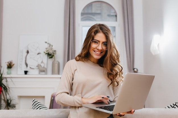 Pleased smart girl with elegant curly hairstyle enjoying photoshoot with laptop
