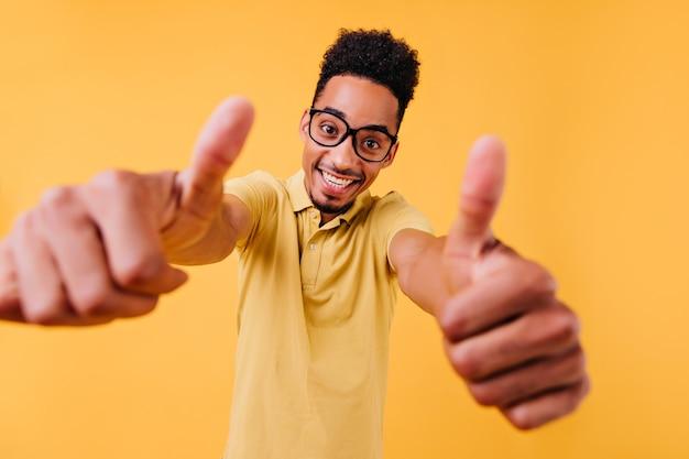 엄지 손가락을 보여주는 기쁘게 똑똑한 사람. 놀라운 아프리카 남성 모델의 실내 사진.