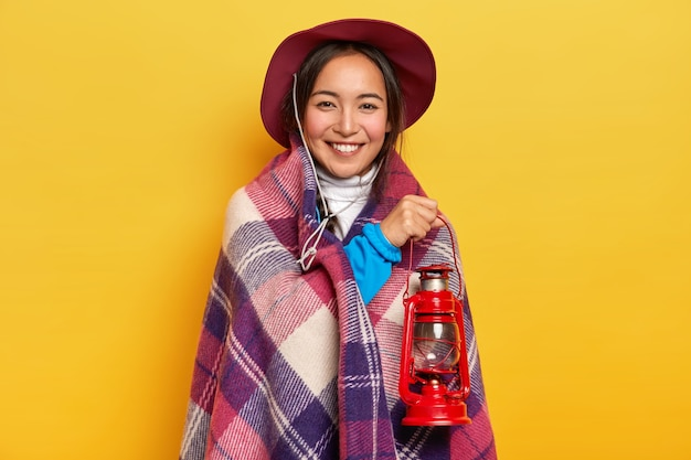 Pleased smiling asian woman wrapped in plaid, holds small gas lantern, wears hat, poses against yellow studio background