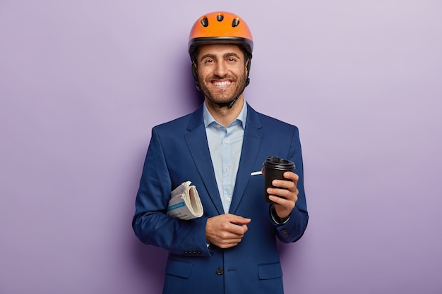 Pleased smiling businessman posing in classy suit and red helmet at the office