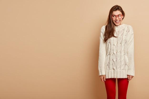 La donna sorridente e soddisfatta indossa gli occhiali, un lungo maglione bianco lavorato a maglia, collant rossi, guarda da parte, è di buon umore, si trova sul muro beige, spazio vuoto per i tuoi contenuti promozionali.