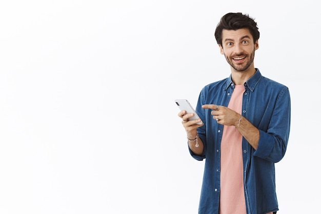 Pleased smiling handsome man with beard in pink t-shirt, shirt, holding smartphone, pointing screen and grin camera as recommend friend log in and try yourself