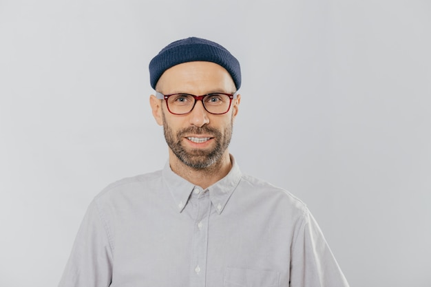 Pleased smiling man wears glasses, hat and shirt