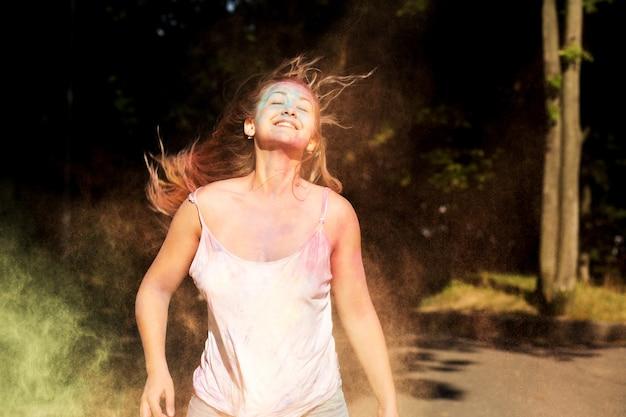 乾いたホーリーのペンキを爆発させてジャンプする髪の風で満足のいく笑顔モデル