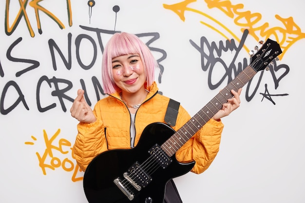 Pleased smiling pink haired teenage girl dreams to become rock star play music on acoustic guitar wears orange jakcet shows mini heart gesture or korean like sign poses against graffiti wall