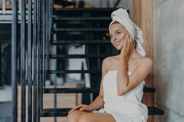 Pleased smiling woman applies face cream, poses on stairs, wrapped in bath towel, smiles gently and has minimal makeup, enjoys softness after taking shower, takes care of skin. wellness concept