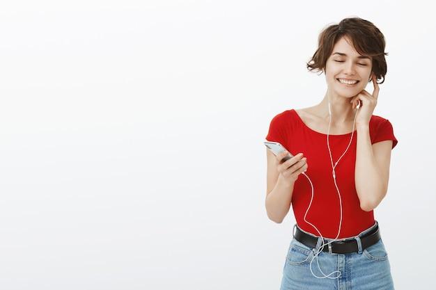 イヤホンで音楽を聴いたり、携帯電話を持ったり、お気に入りの曲を楽しんだりして喜んでいる笑顔の女性
