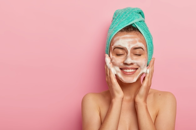 Pleased smiling woman washes face with cleansing gel, has soap on complexion, keeps eyes shut, wears wrapped towel on head, has naked body