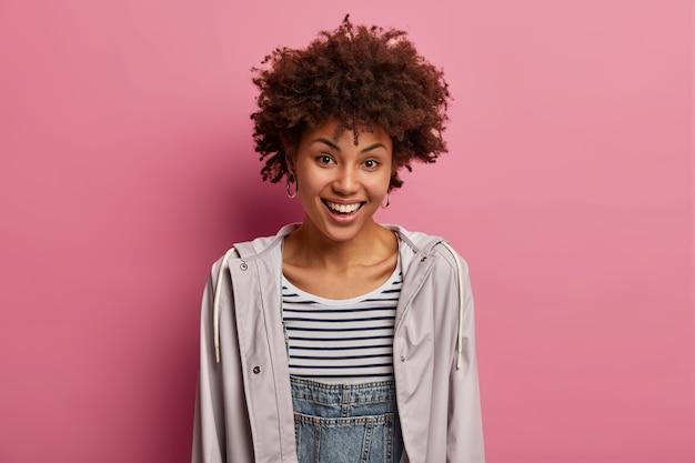アフロの髪型、魅力的な表情で満足している笑顔の女性は、ポジティブなニュースを見つけます