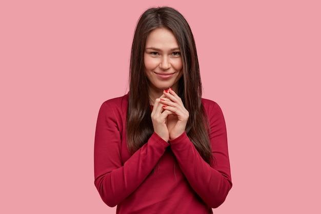 Donna sorridente soddisfatta dall'aspetto accattivante, tiene le mani unite vicino al mento, indossa un maglione rosso, ha intenzione di dire piacevoli notizie al marito