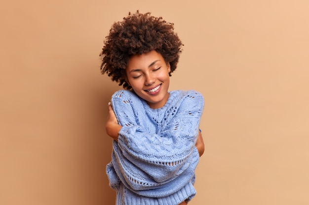 Pleased smiling woman with bushy curly hair embraces herself with love enjoys softness of new jumper feels comfortable and delighted closes eyes in satisfaction isolated over beige wall