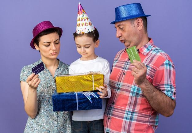 Figlio contento con cappello da festa che tiene e guarda scatole regalo in piedi con sua madre e suo padre che indossano cappelli da festa e in possesso di carte di credito isolate sul muro viola con spazio di copia