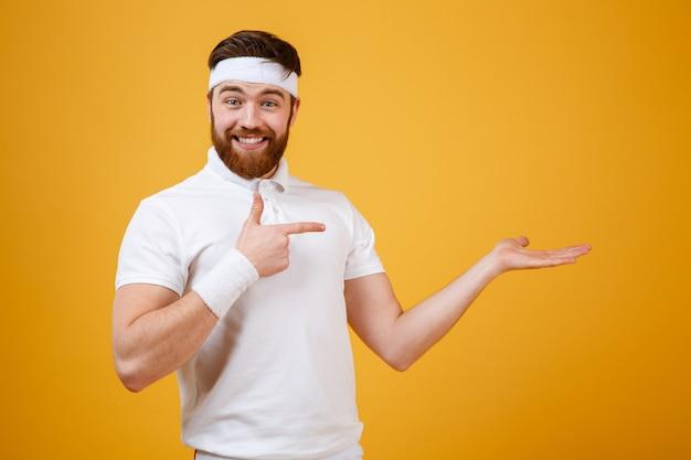 Довольный спортсмен, указывая на невидимое copyspace на фунт