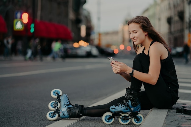 Pleased sporty woman wears sportsclothes rollerblades sits on road checks newsfeed via smartphone takes break after inline skating poses against blurred city background engaged in healthy lifestyle
