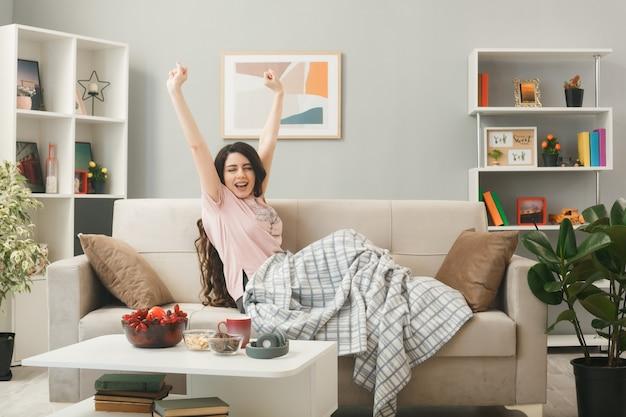 Довольно протягивая руку, обернутую в клетку, молодая девушка сидит на диване за журнальным столиком в гостиной