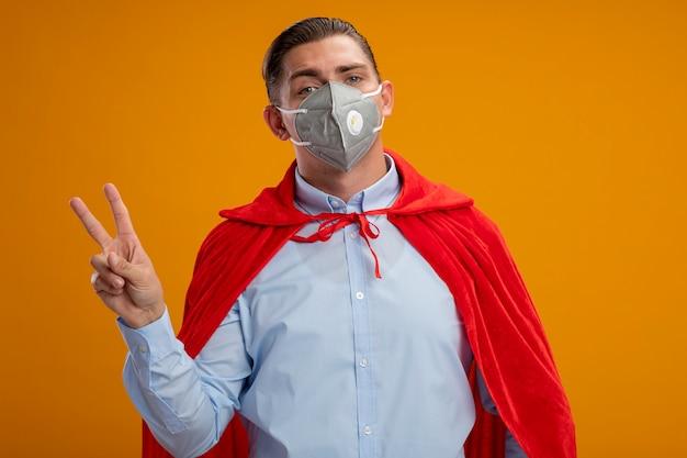 オレンジ色の背景の上に立っているvサインを示すカメラを見て保護フェイシャルマスクと赤いマントでスーパーヒーローのビジネスマンを喜ばせる