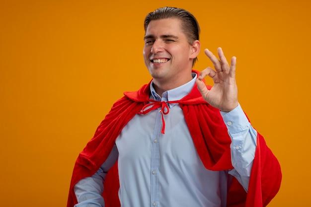 オレンジ色の背景の上に立っているokサインを広く示して笑っているカメラを見て赤いマントのスーパーヒーローのビジネスマンを喜ばせる