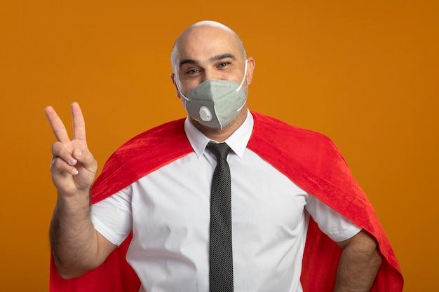 Soddisfatto uomo d'affari super eroe in maschera facciale protettiva e mantello rosso che mostra il segno v