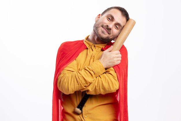 Pleased superhero man with red cloak holds baseball bat isolated on white wall