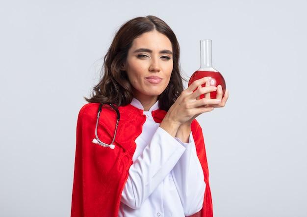 La superdonna soddisfatta in uniforme del medico con il mantello rosso e lo stetoscopio tiene il liquido chimico rosso nel pallone di vetro isolato sulla parete bianca