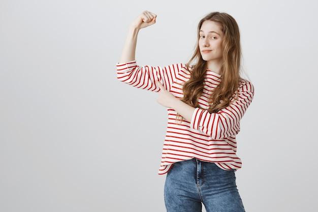 Pleased teenage girl flex biceps and smirk satisfied