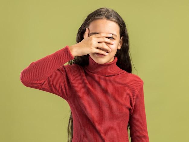 올리브 녹색 벽에 격리된 손가락을 통해 카메라를 바라보는 손으로 눈을 덮고 있는 카메라를 보고 있는 행복한 10대 소녀