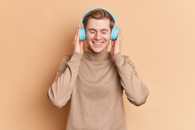 Pleased teenage guy relaxes with closed eyes listens favorite song via wireless blue headphones uses music app smiles gladfully wears casual jumper poses