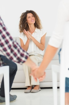 Pleased therapist looking at reconciled couple holding hands