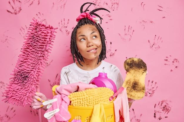 汚れた顔で幸せな思いやりのある忙しい女性は、掃除がモップを保持し、スポンジが乱雑なアイテムと化学洗剤でバスケットの近くの部屋のスタンドで無秩序を掃除しようとした後のアパートを想像します