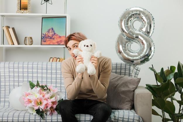 Felice inclinando la testa bel ragazzo durante la felice giornata delle donne con in mano un orsacchiotto seduto sul divano in soggiorno