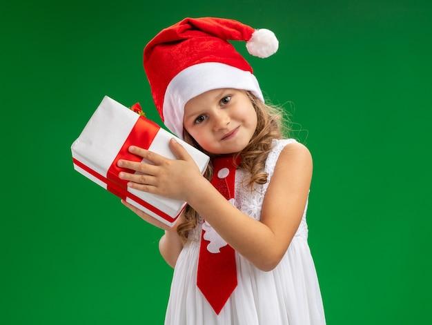 Довольно наклонив голову маленькая девочка в новогодней шапке с галстуком держит подарочную коробку, изолированную на зеленой стене
